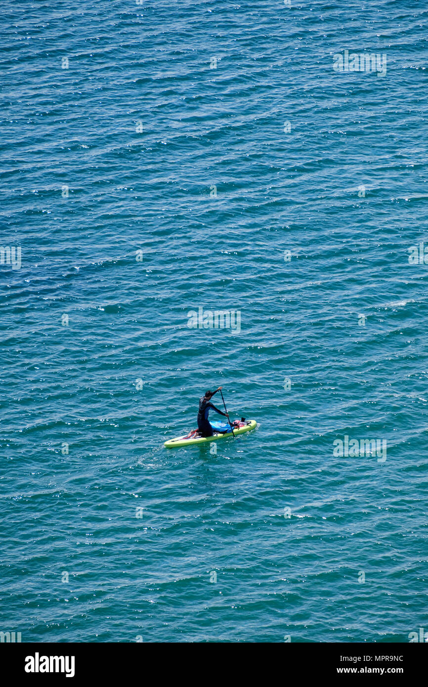 MAN IN WET SUIT ON PADDLE BOARD AT SEA,LYDSTEP PEMBROKESHIRE WALES UK - Stock Image