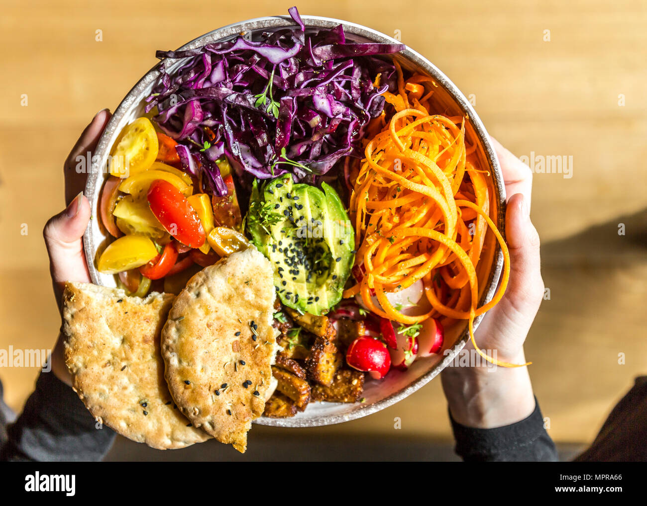 Girl holding veggie bowl with tomato, tofu, red cabbage, avocado, carrot, red redish, cress, black sesame and pita bread - Stock Image