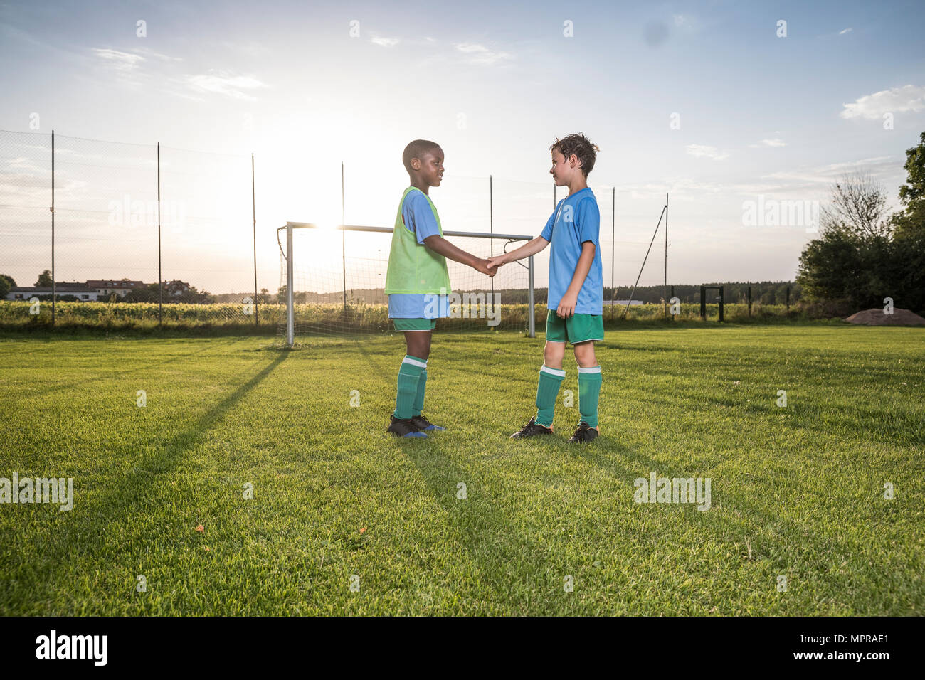 Young football players shaking hands on football ground - Stock Image