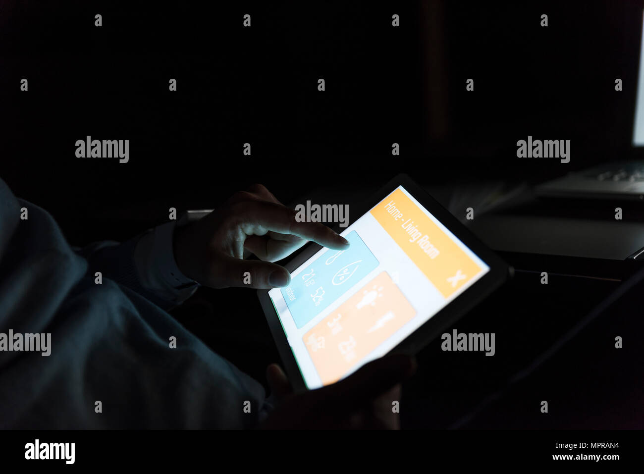 Businessman working on tablet at dark, close-up - Stock Image