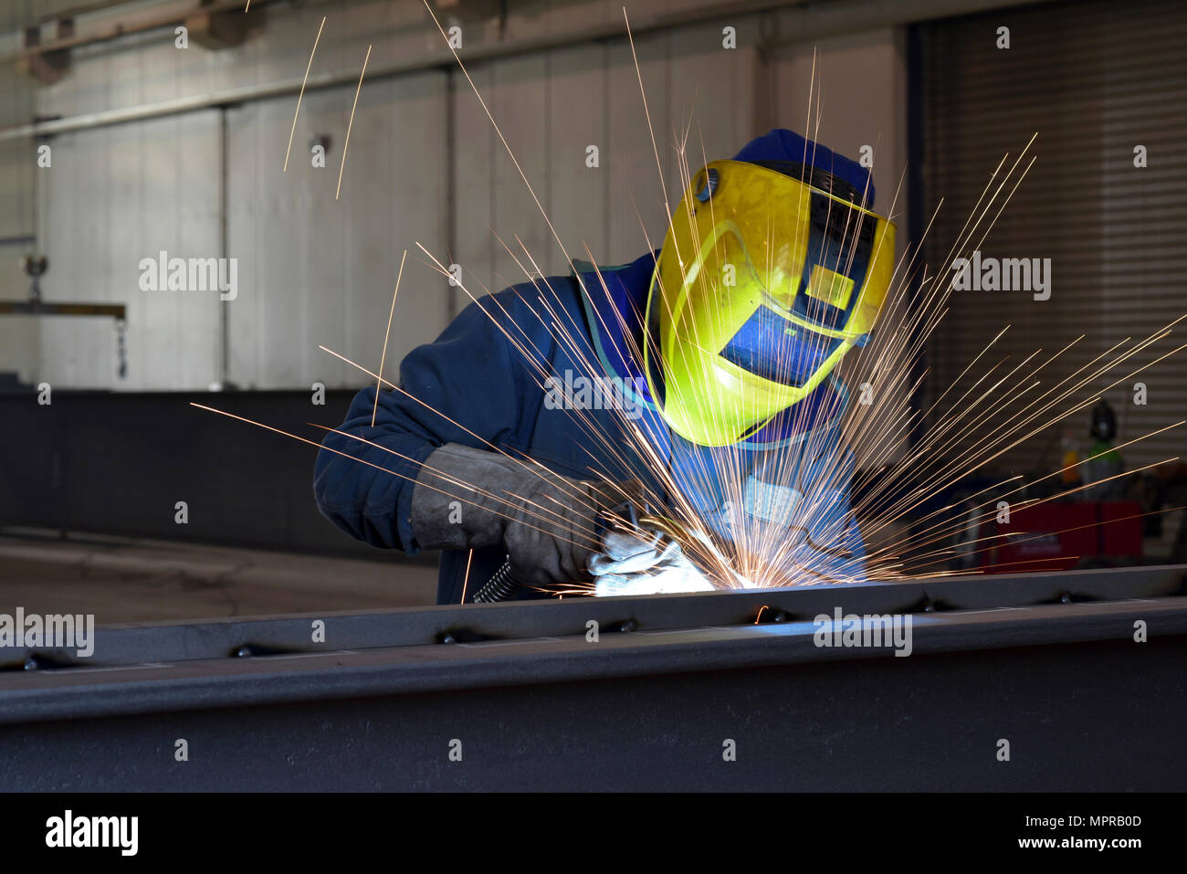 Welder at work in factory - Stock Image