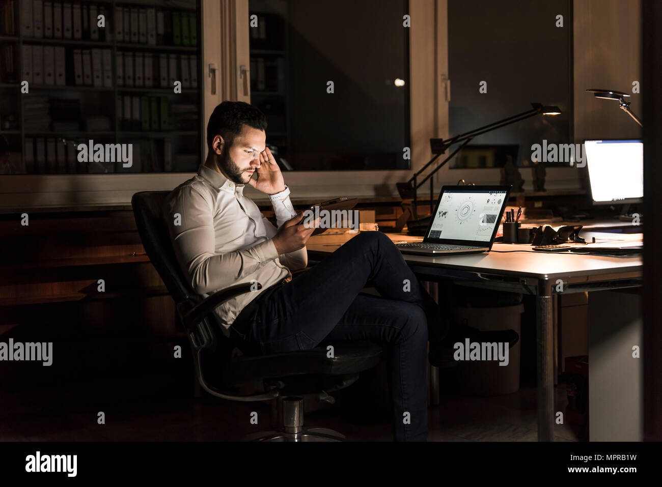 Businessman using tablet in office at night - Stock Image