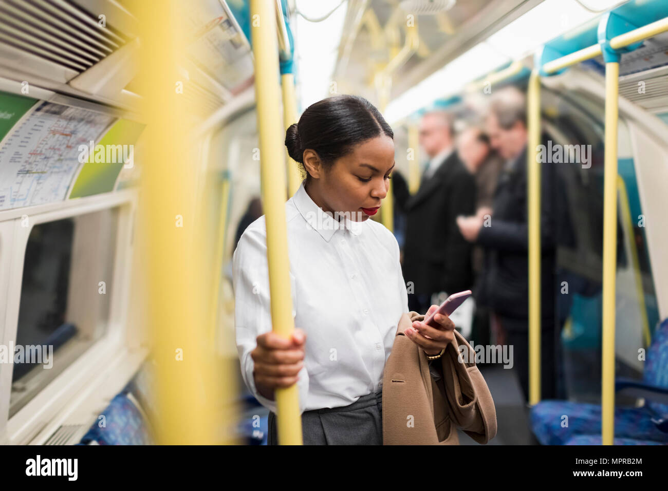UK, London, businesswoman in underground train looking at cell phone - Stock Image
