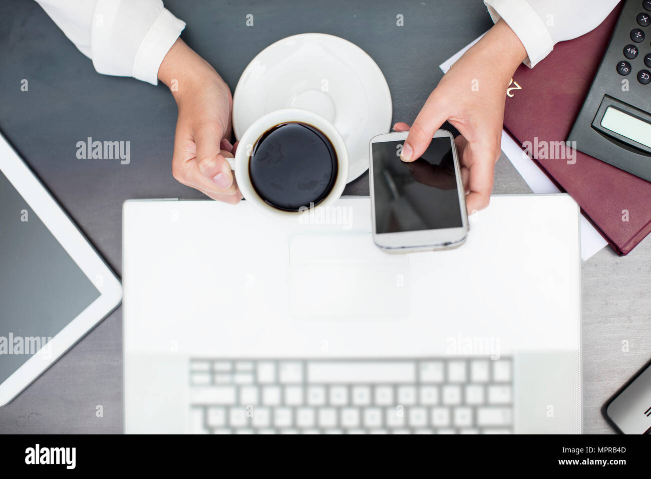 Woman with cup of coffee using smartphone, laptop - Stock Image