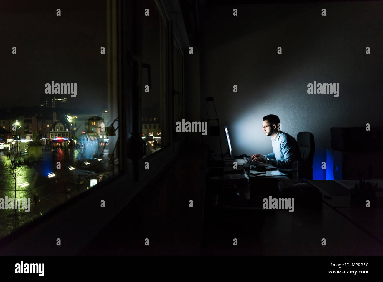 Businessman working on computer in dark office - Stock Image