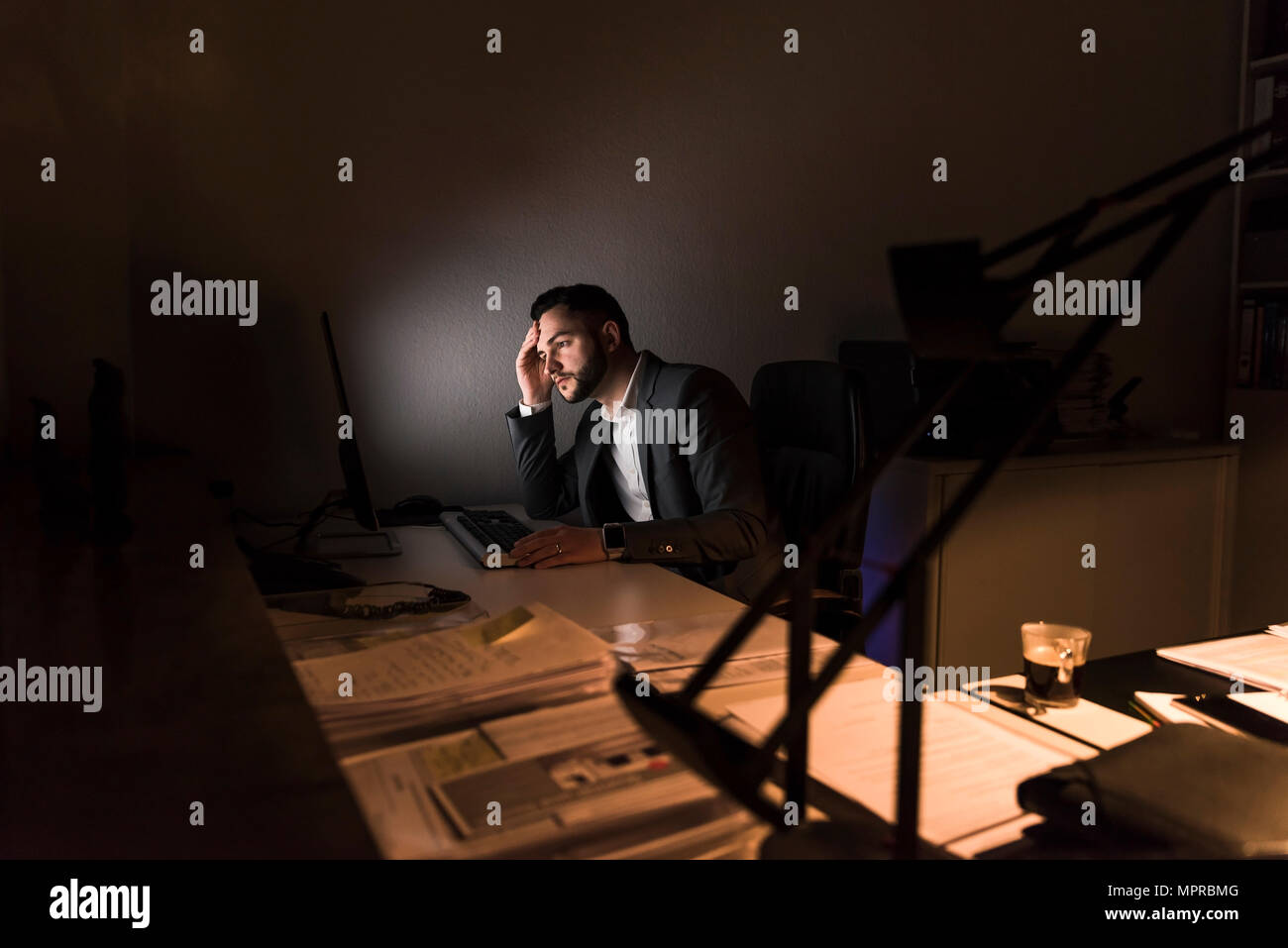 Pensive young businessman sitting at desk in office at night - Stock Image