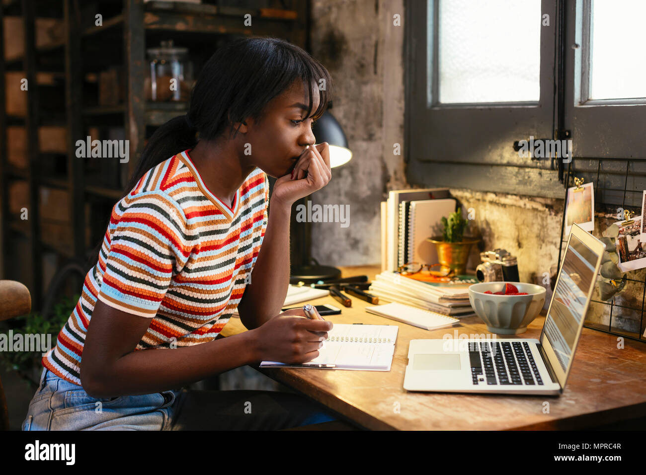 Pensive young woman sitting at desk in a loft looking at laptop - Stock Image