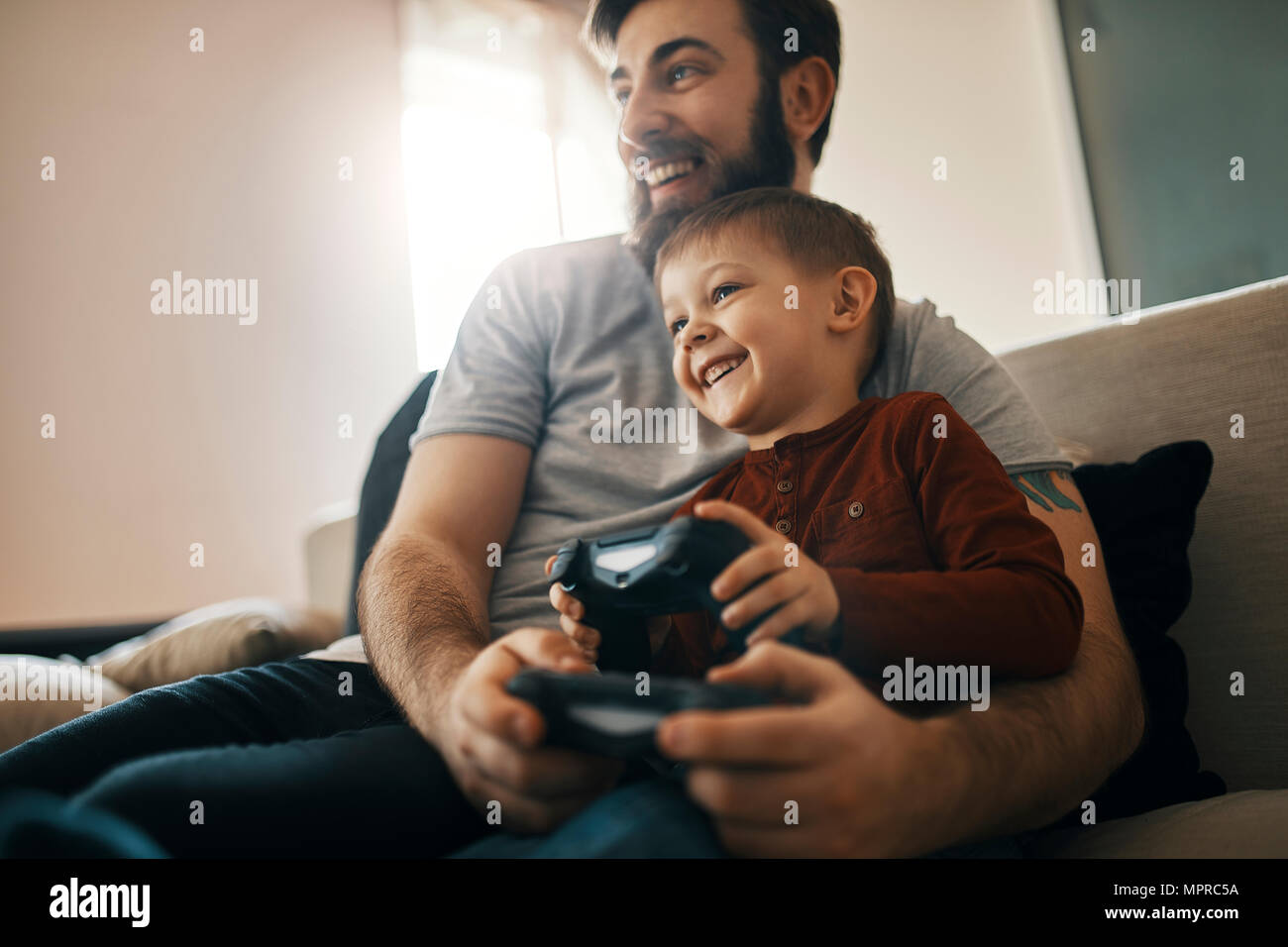 Happy father and little son sitting together on the couch playing computer game - Stock Image