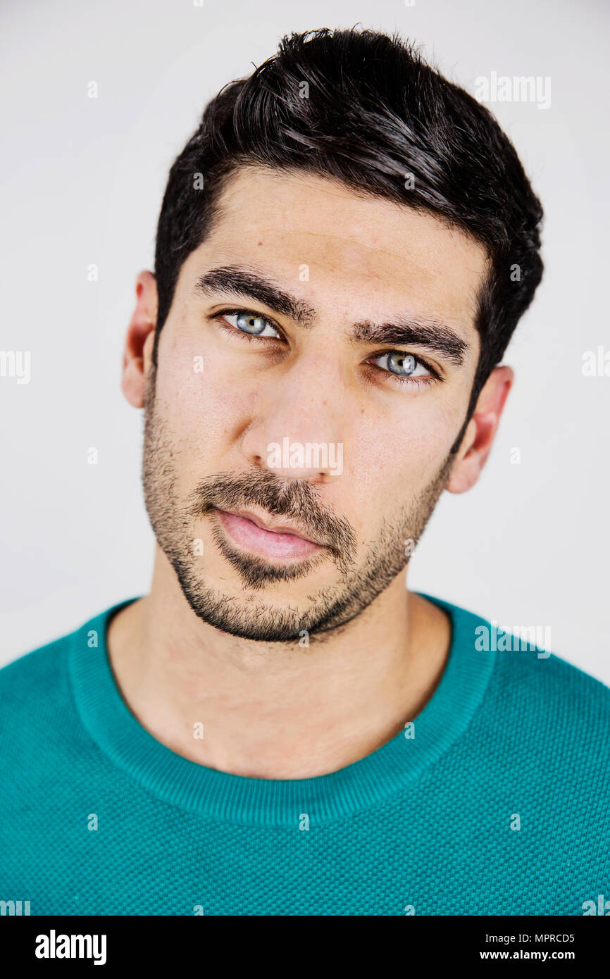 Portrait of young man with blue eyes and stubble - Stock Image