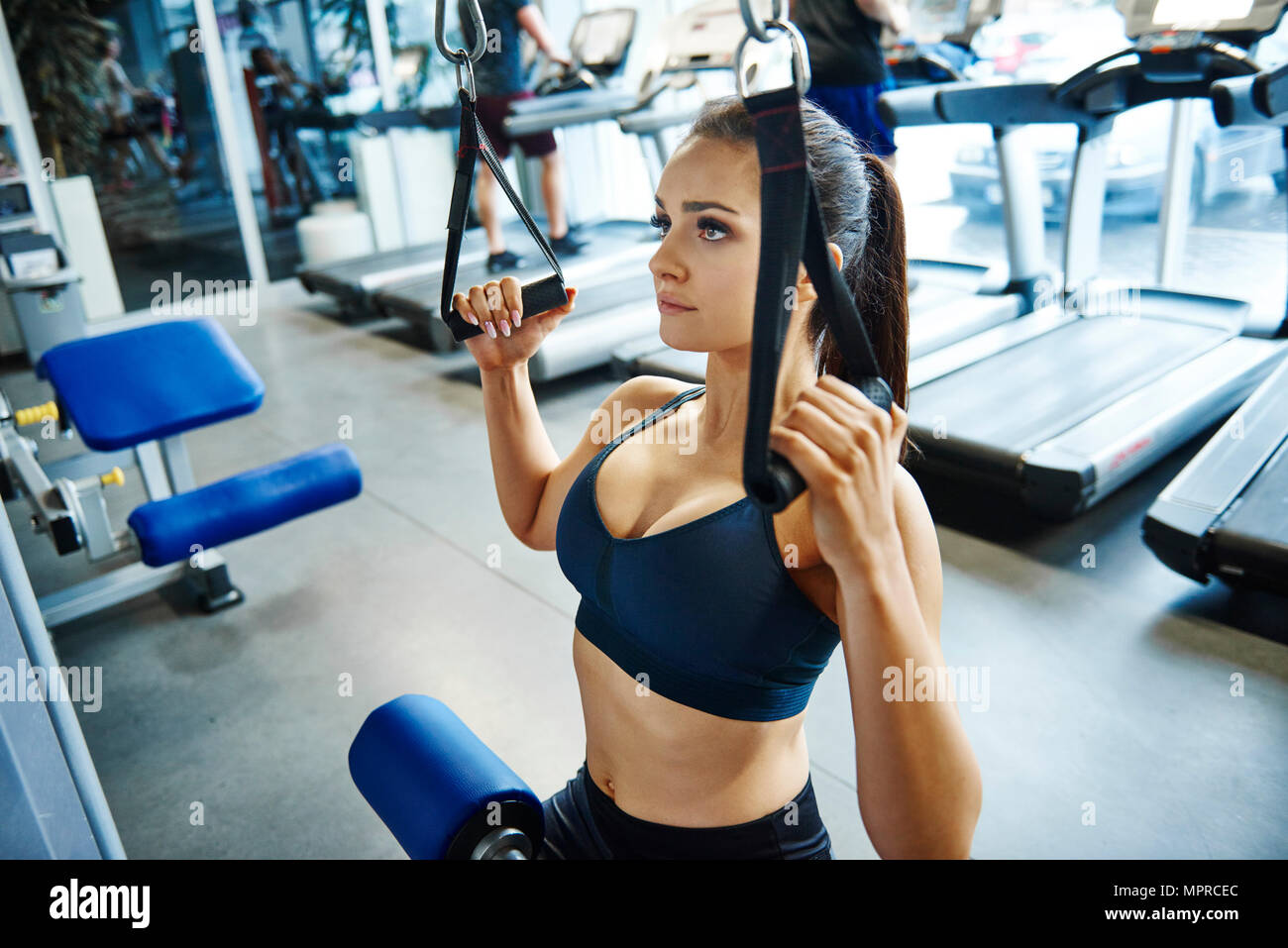 Woman training with exercise machine in the gym - Stock Image