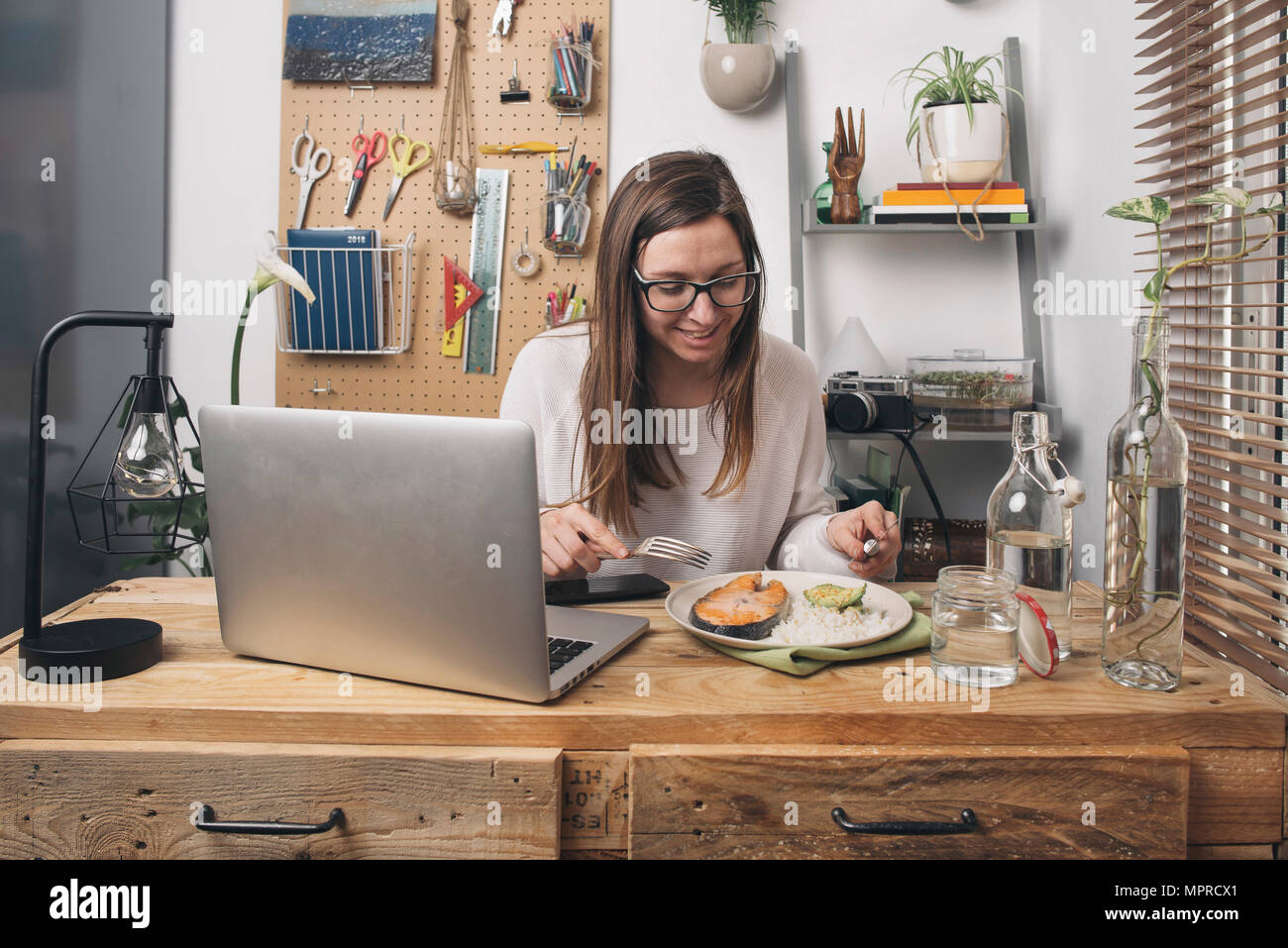 Woman having lunch at wooden table with laptop - Stock Image