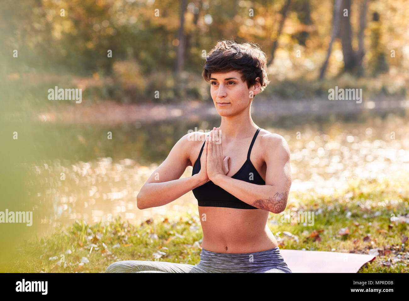 Mid adult woman in forest practicing yoga, meditation - Stock Image