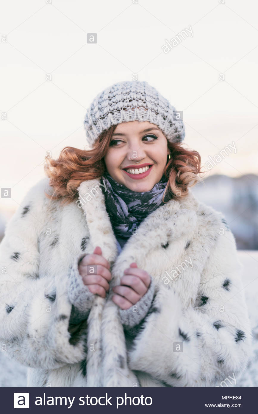 Portrait of fashionable young woman with curly hair wearing wool cap in winter - Stock Image