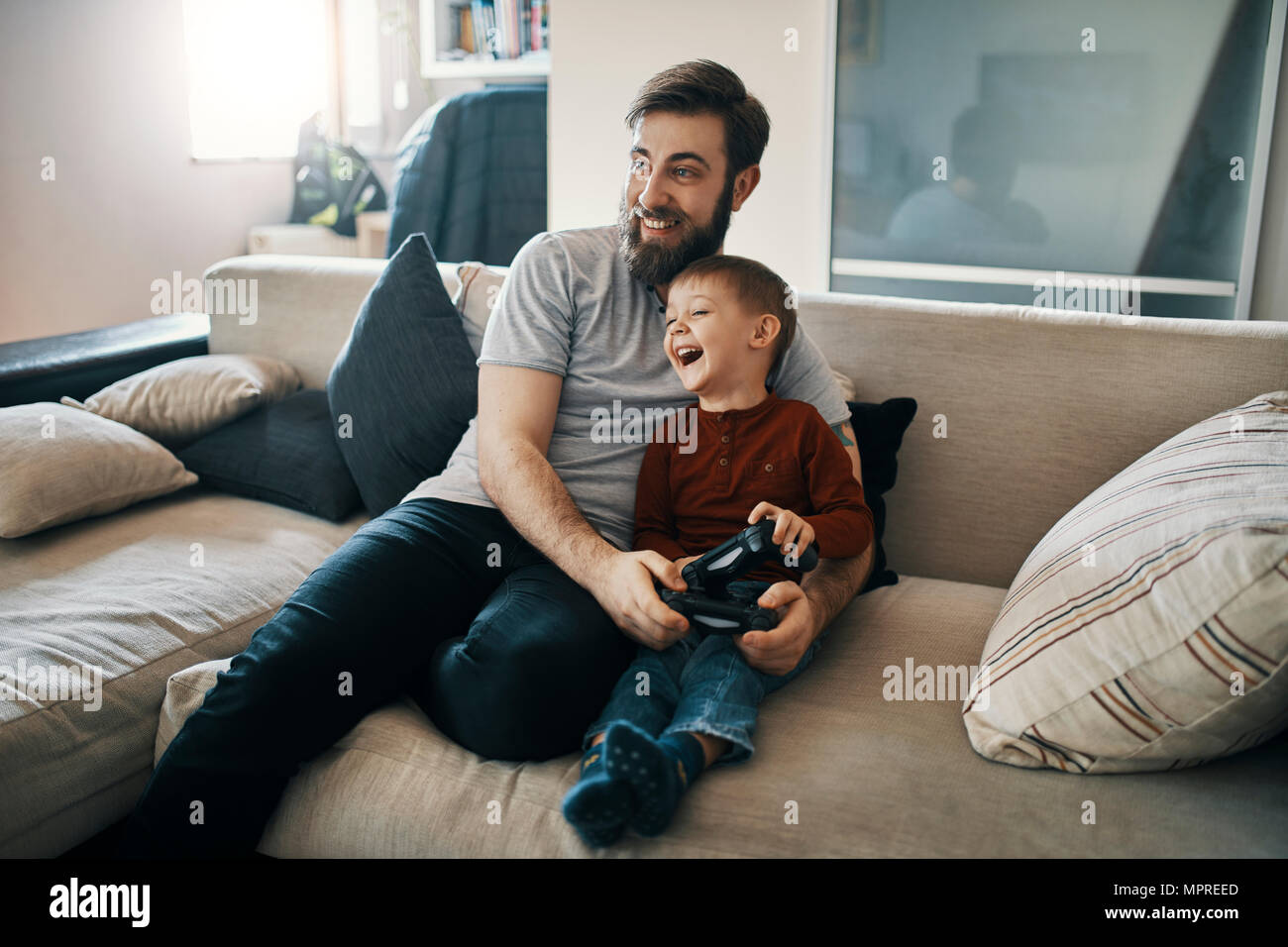 Happy father and son sitting together on the couch playing computer game - Stock Image
