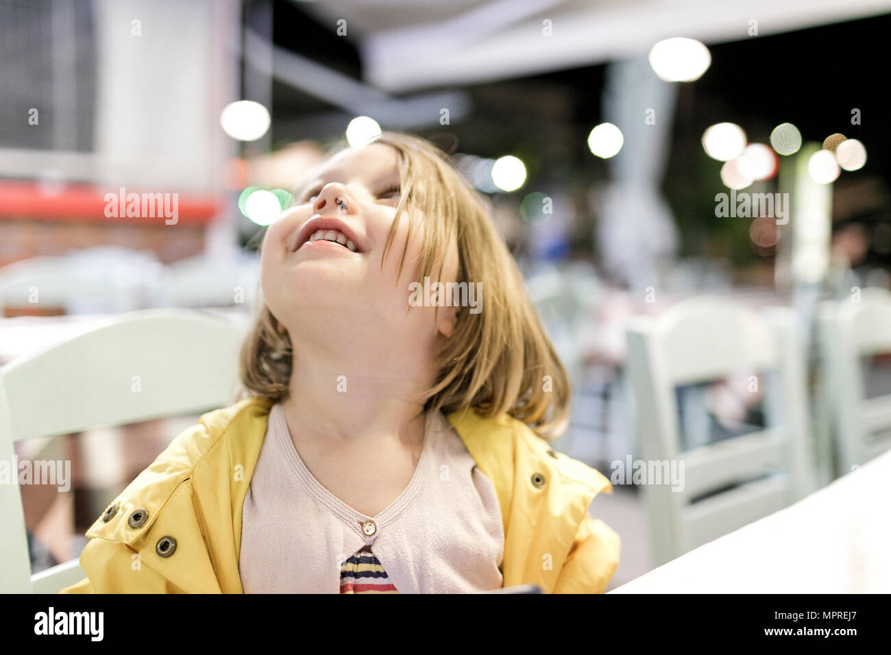 Little girl sitting in a restaurant watching something - Stock Image