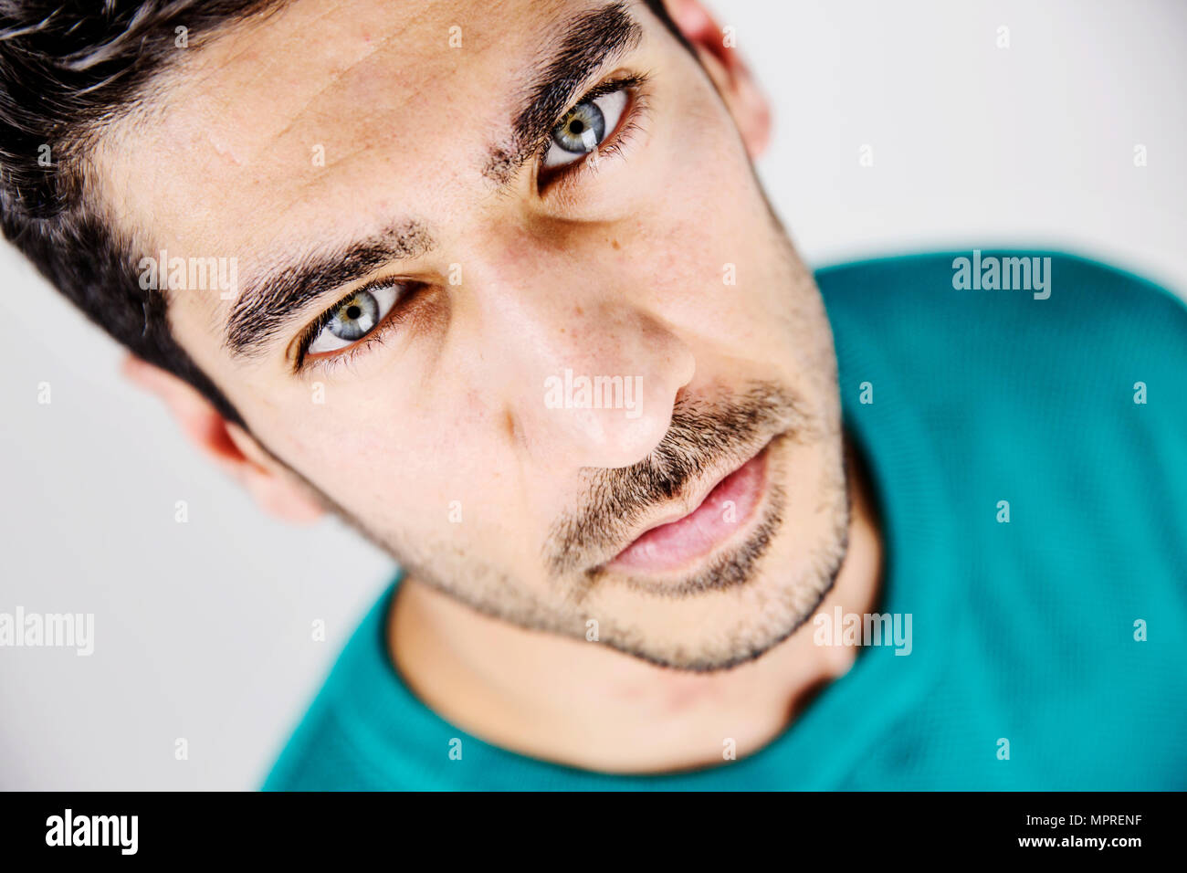 Portrait of serious young man with blue eyes and stubble - Stock Image