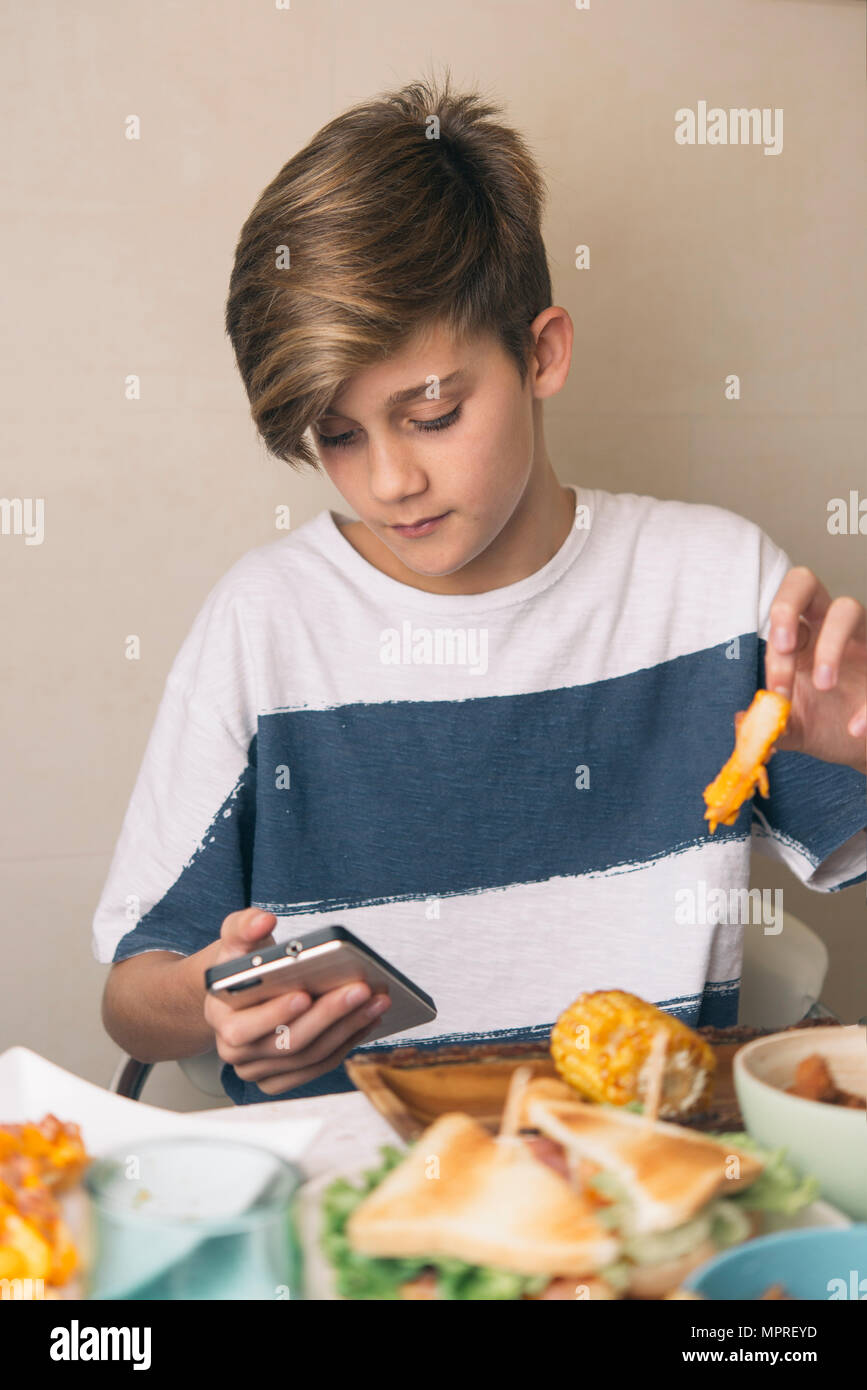 Boy eating at dining table and looking at the phone at the same time - Stock Image