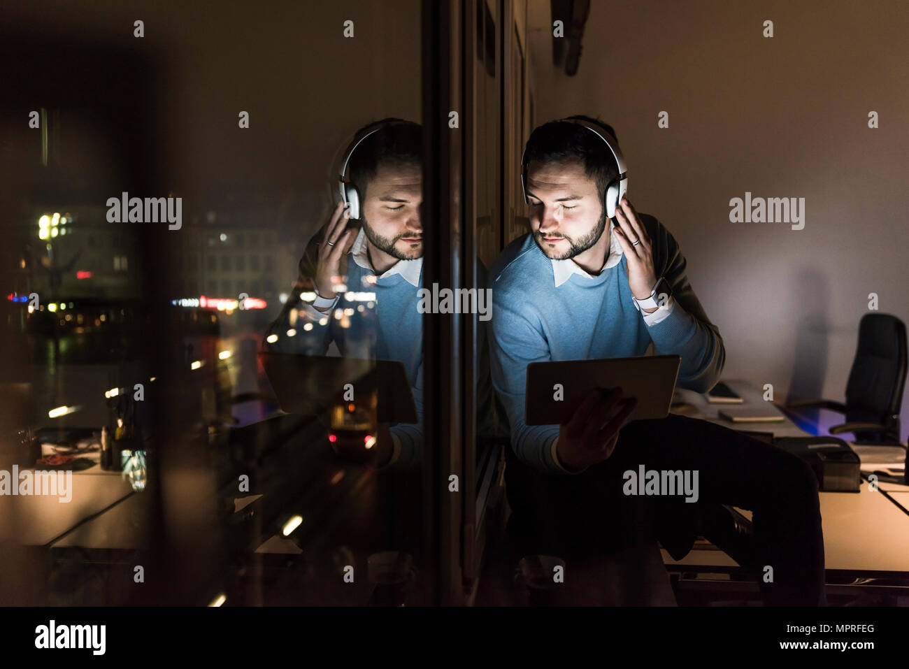 Businessman sitting on window sill in office at night listening music with headphones - Stock Image
