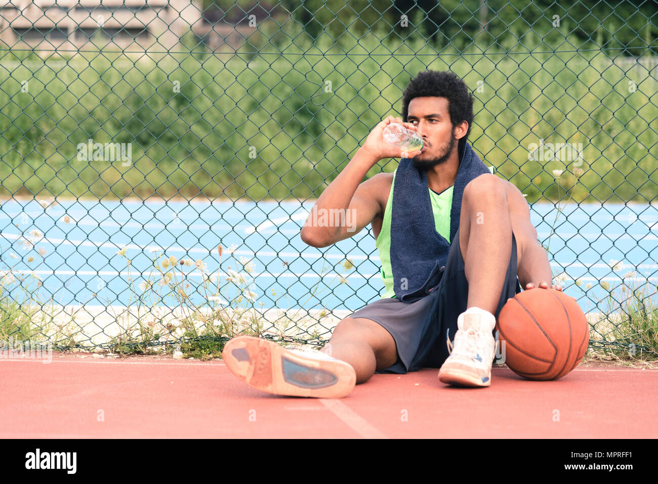 Young basketball player drinking from water bottle - Stock Image