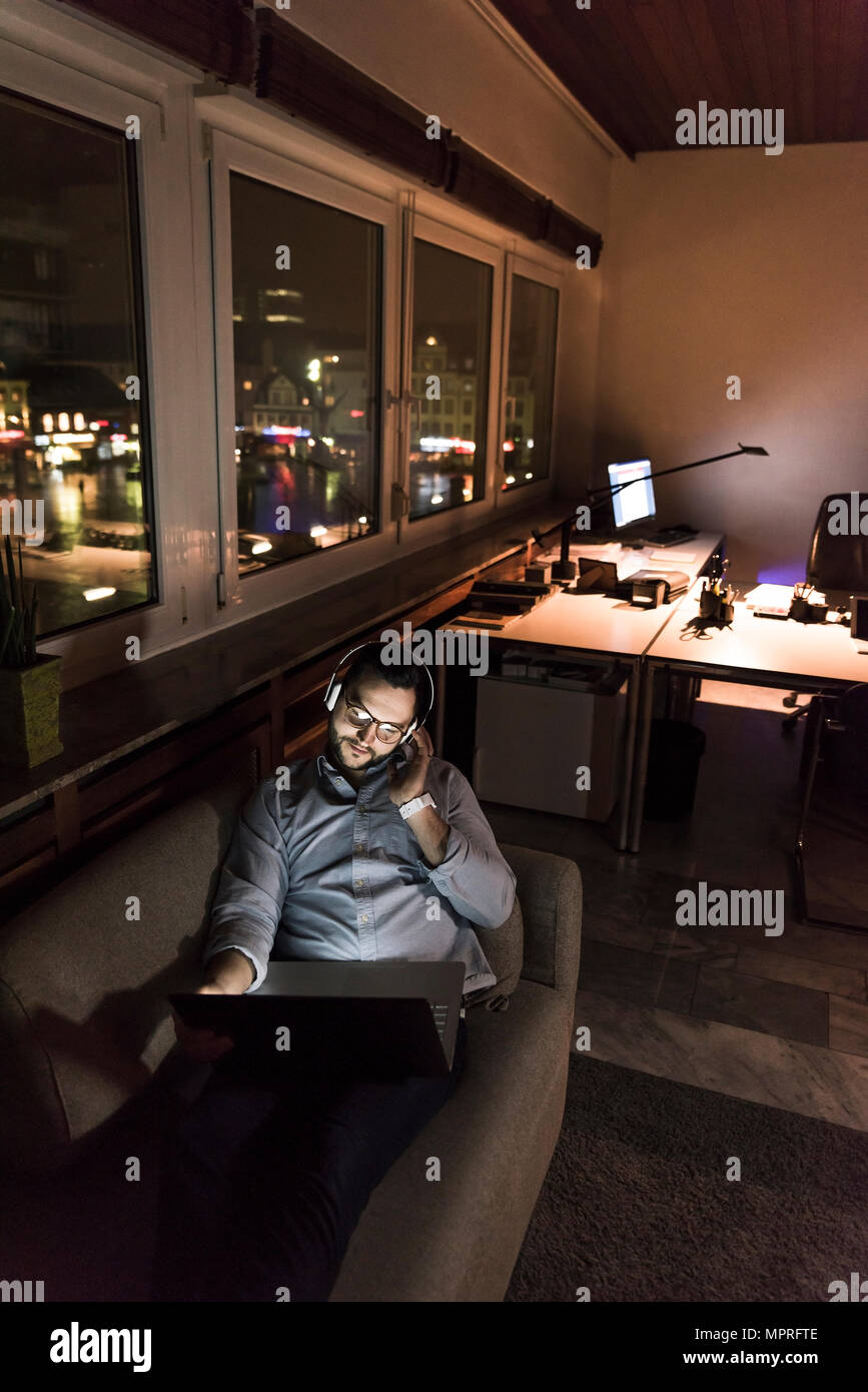 Businessman in office sitting on the couch at night using laptop and headphones - Stock Image