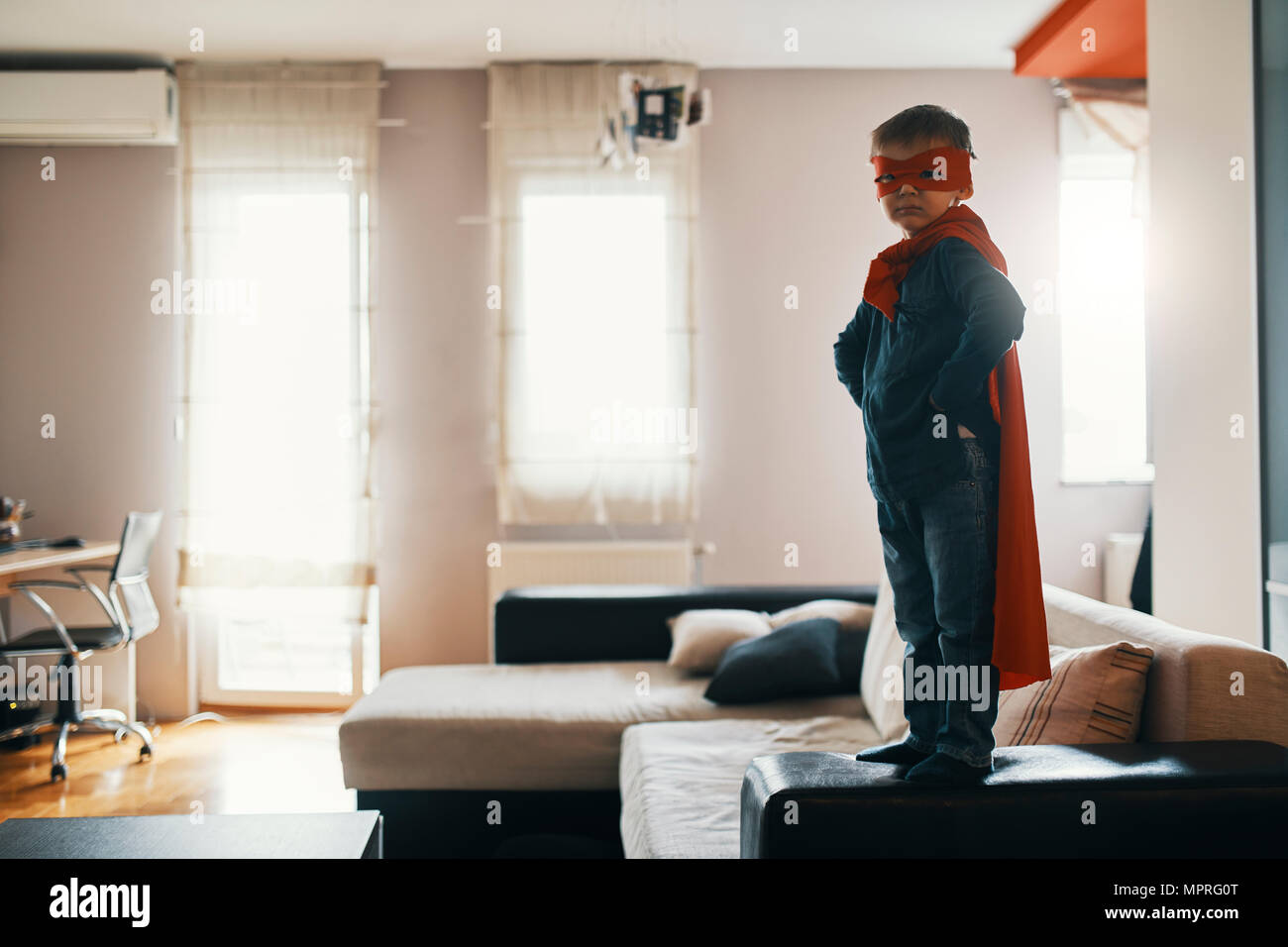 Little boy dressed up as a superhero standing on coffee table at home - Stock Image