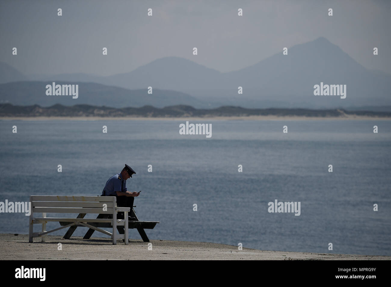 Garda Alan Gallagher uses his mobile phone as he waits on the shore for voters to show up after carrying the polling box for the referendum on liberalising abortion law a day early for the few people that live off the coast of Donegal on the island of Inishbofin, Ireland. - Stock Image