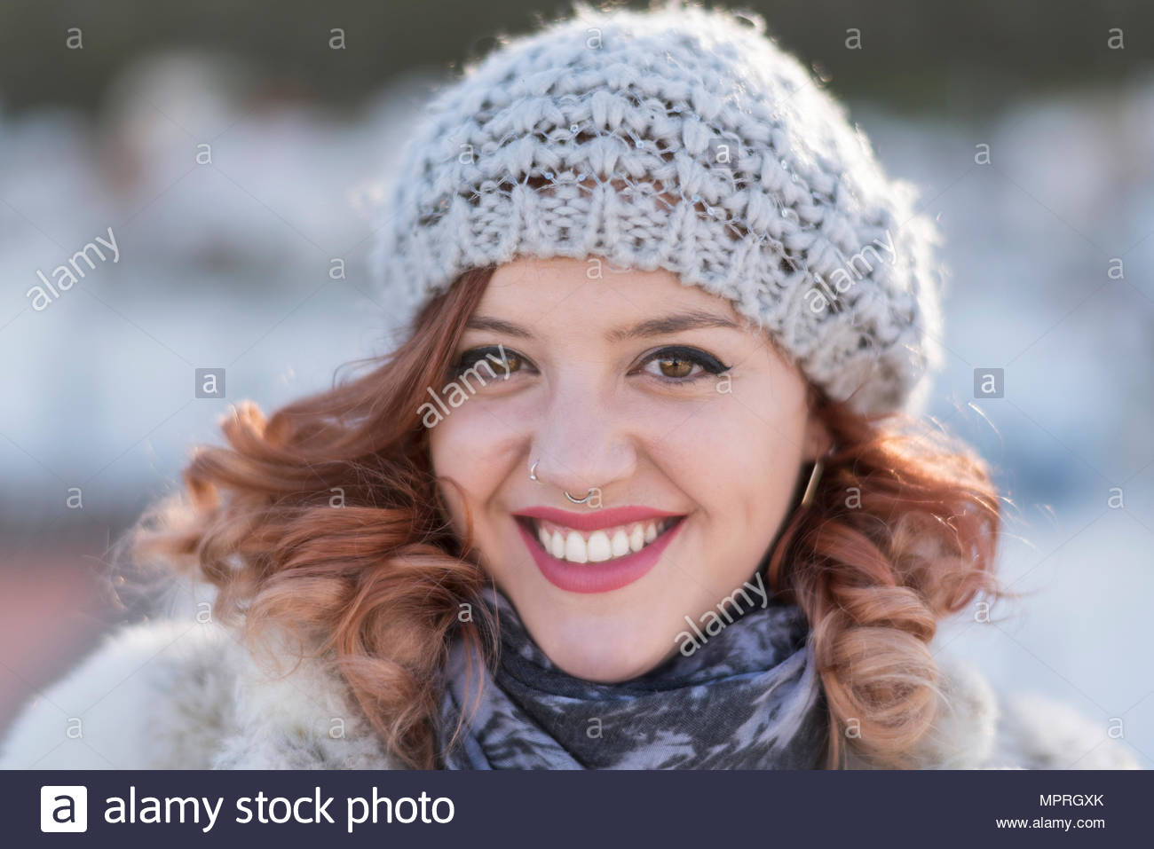 Portrait of laughing young woman with curly hair wearing wool cap and nose piercing - Stock Image