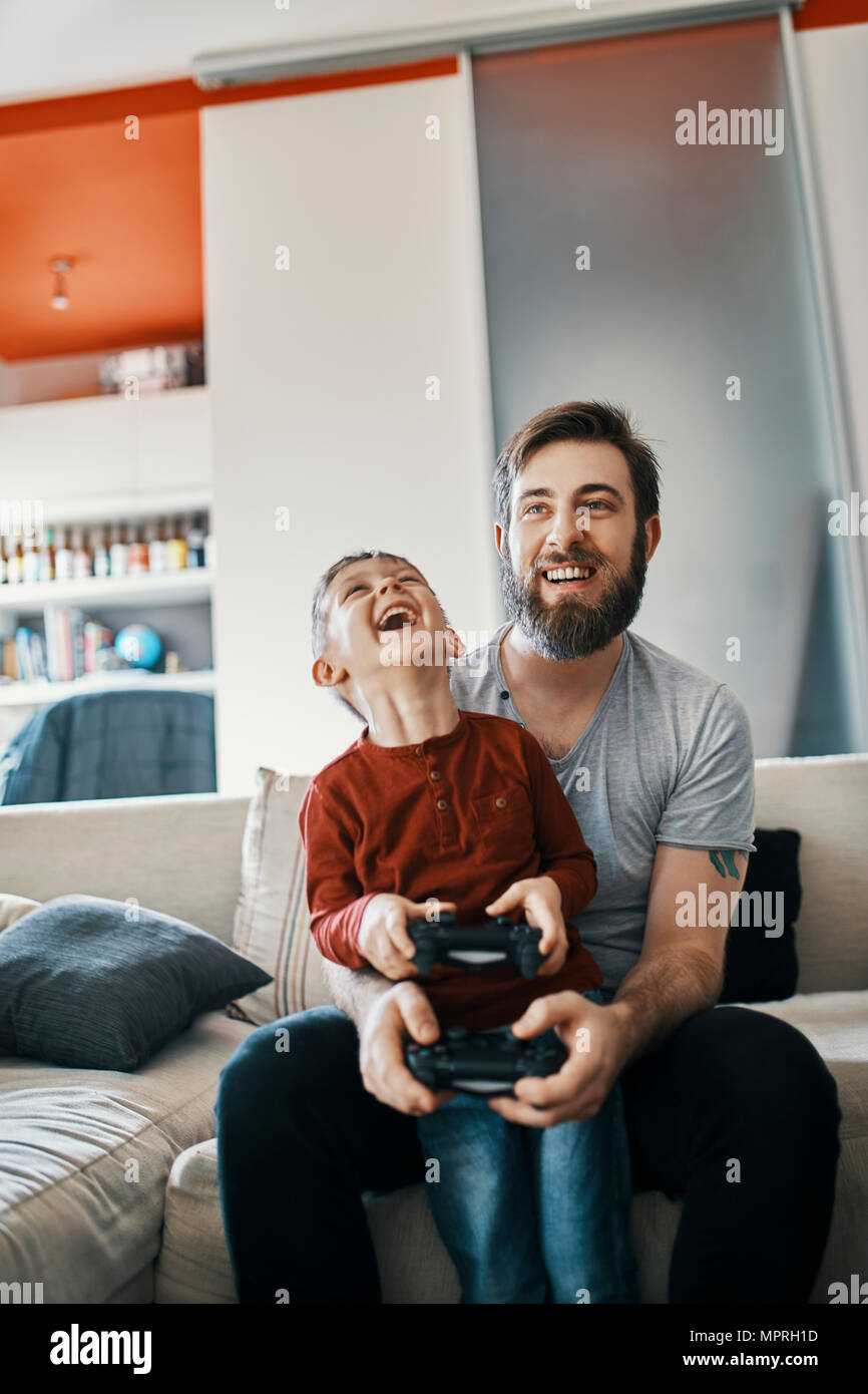 Father and son sitting together on the couch playing computer game - Stock Image