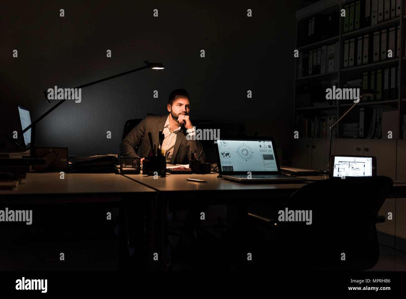 Pensive businessman sitting at desk in office at night - Stock Image