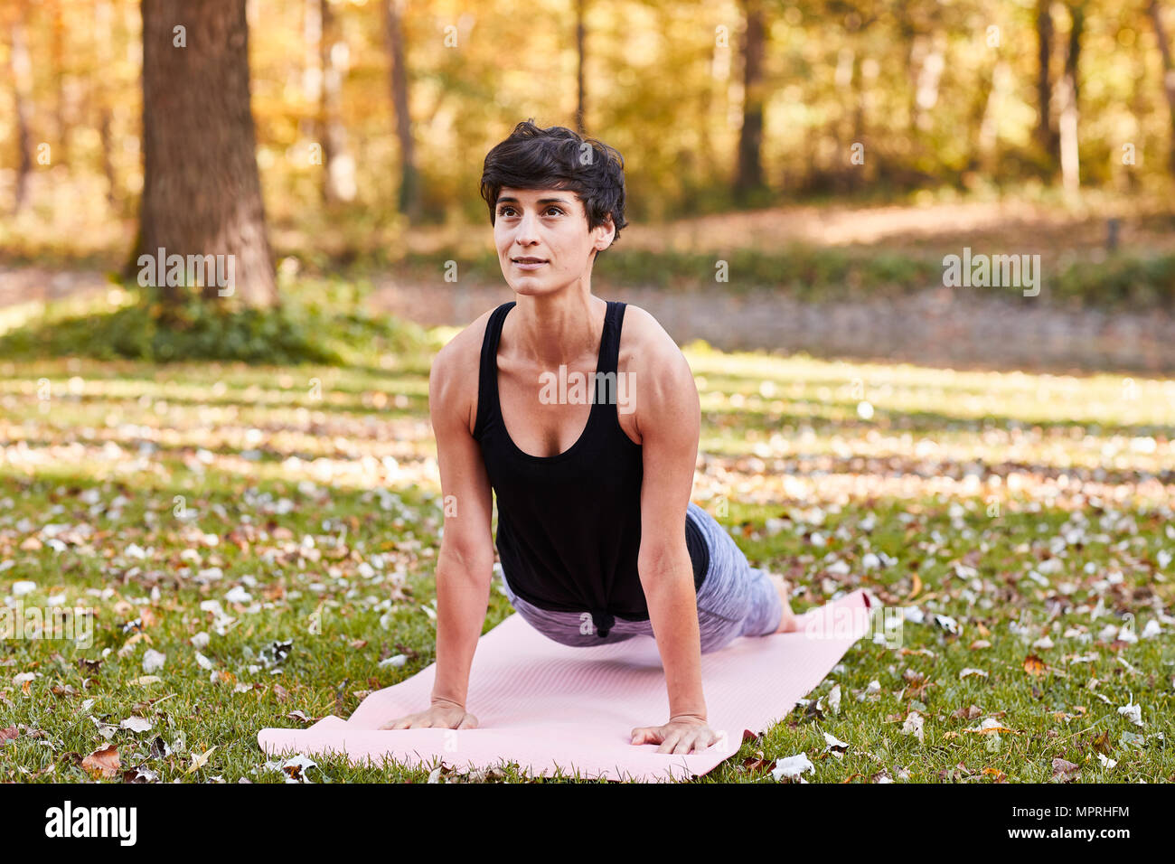 Mid adult woman in forest practicing yoga, cobra pose - Stock Image