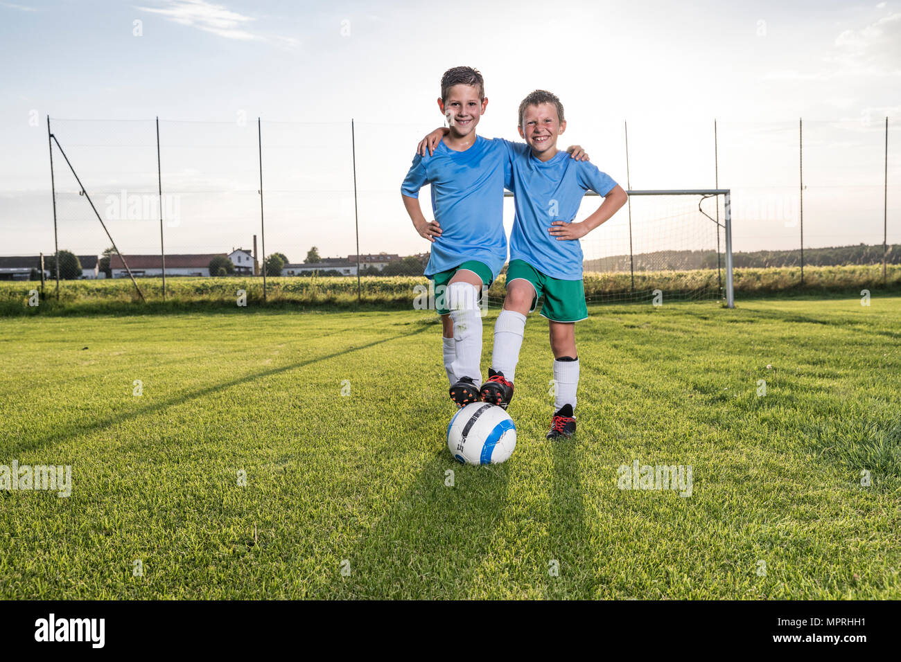 Smiling young football players embracing on football ground - Stock Image