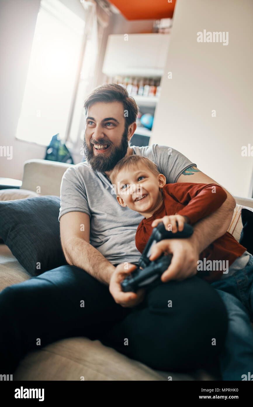 Laughing father and little son sitting together on the couch playing computer game - Stock Image