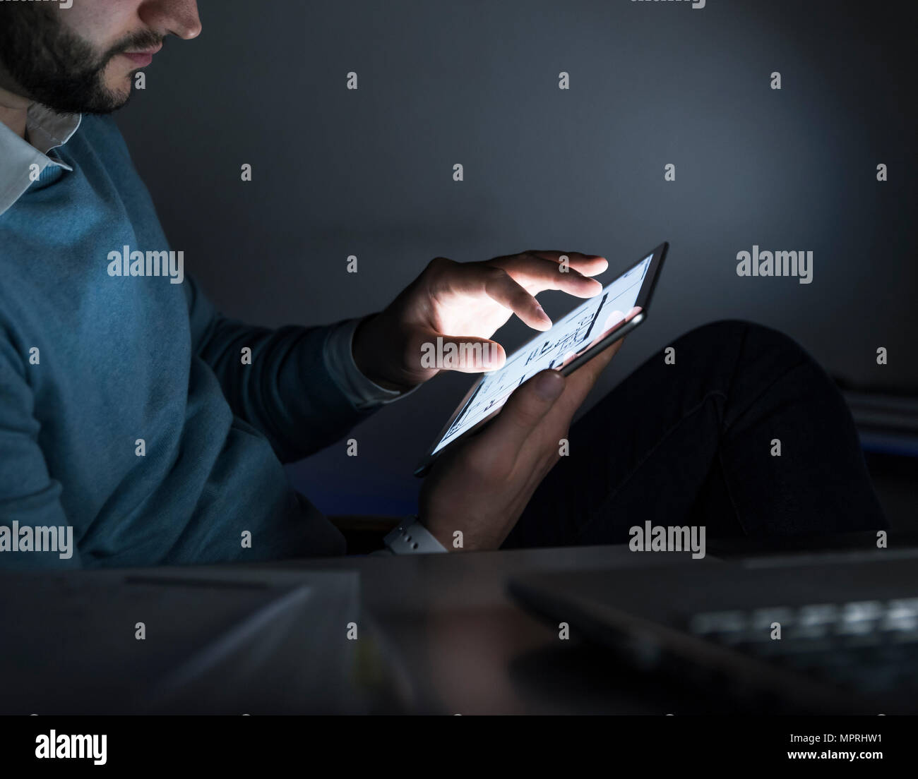Businessman working on tablet in office at night, close-up - Stock Image