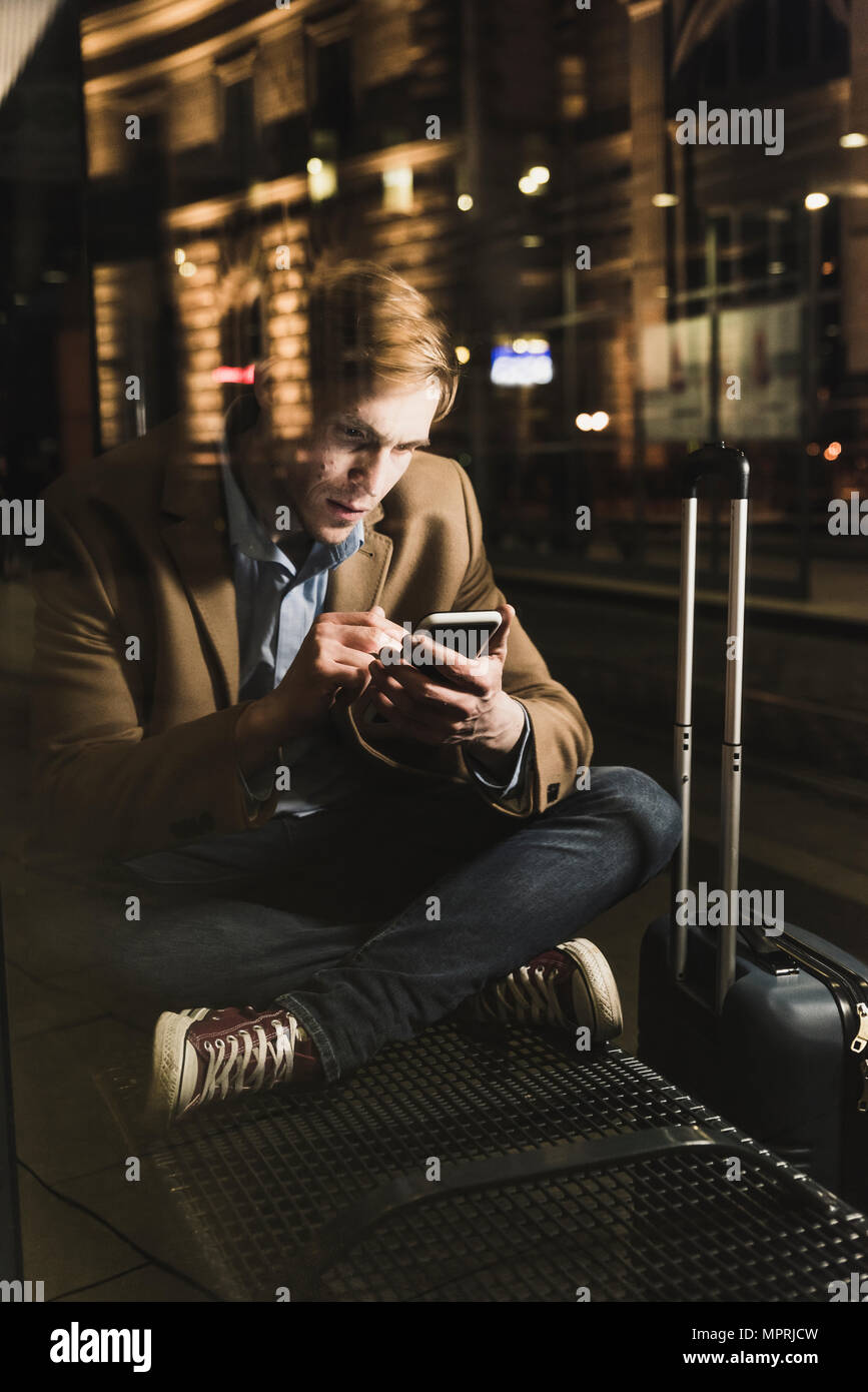 Businessman using cell phone at tram station at night - Stock Image