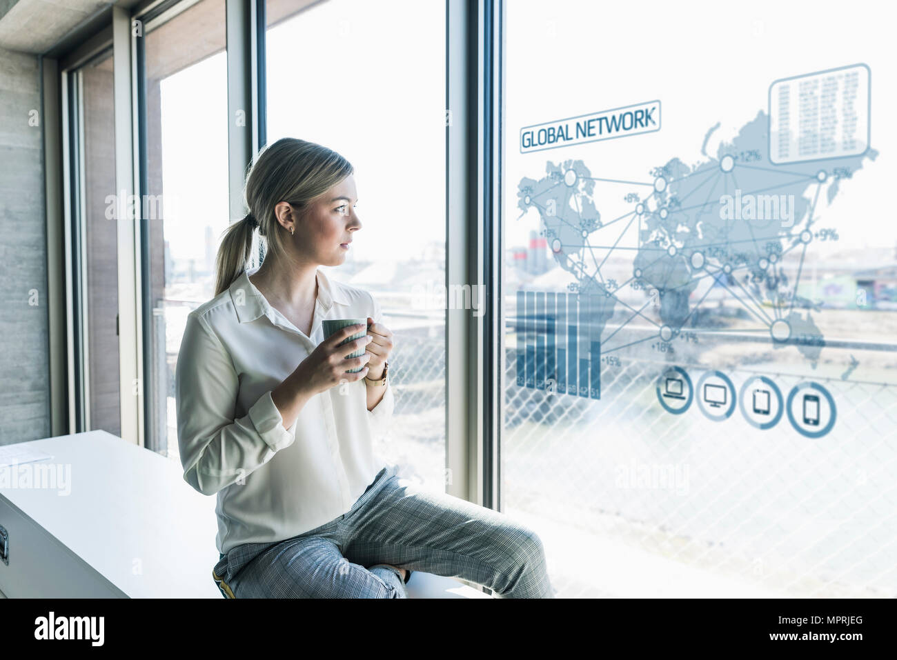 Young businesswoman looking at virtual world map at window pane in office - Stock Image