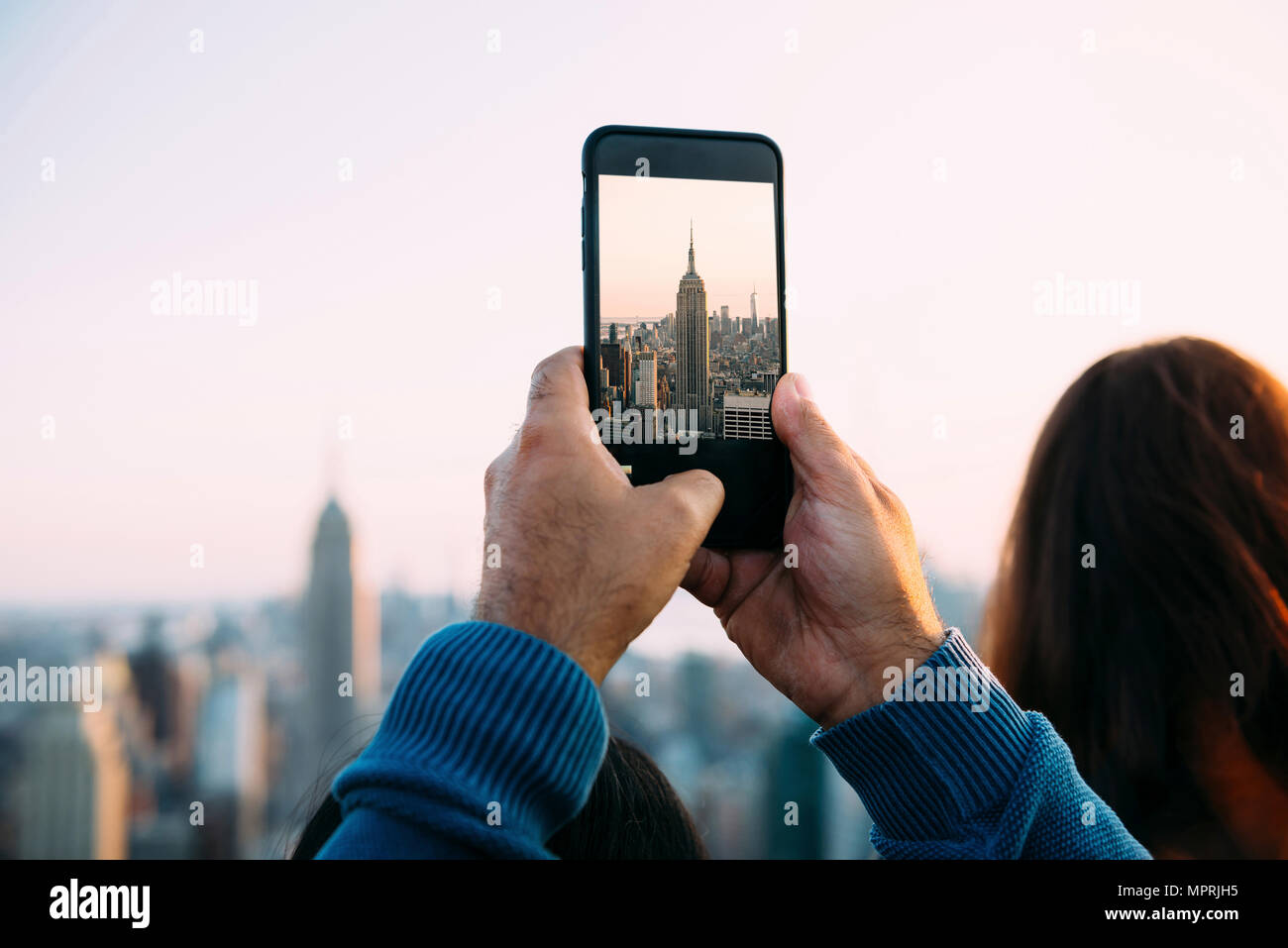 USA, New York City, man's hands taking a photo of Empire State Building with smartphone - Stock Image