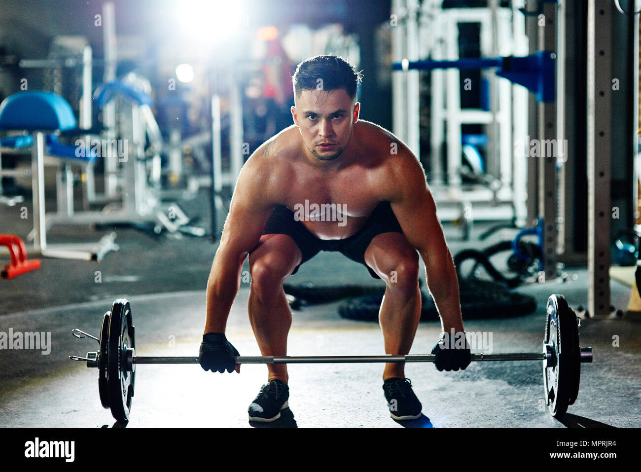 Man lifting barbell in gym - Stock Image