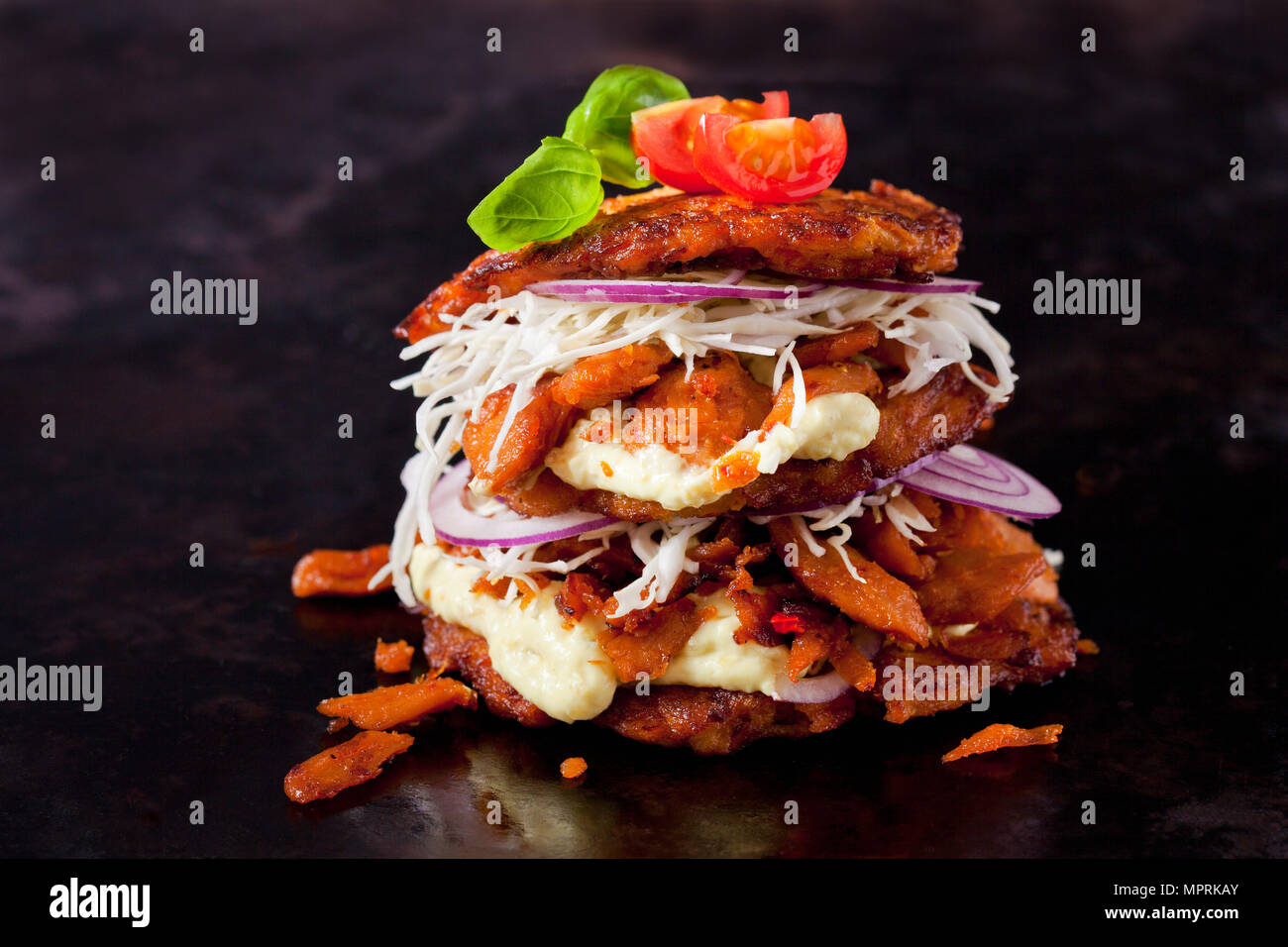Veggie Burger made of potato fritters,  sweet potatoes, soy meat, remoulade and Barbecue sauce - Stock Image