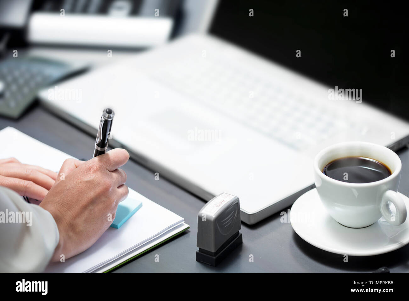 Making notes while working on laptop - Stock Image