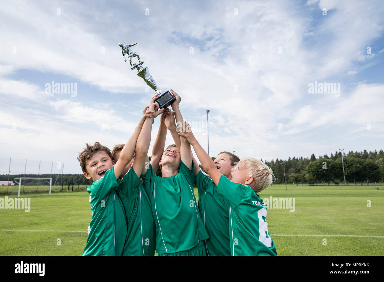 Young football players cheering with cup - Stock Image