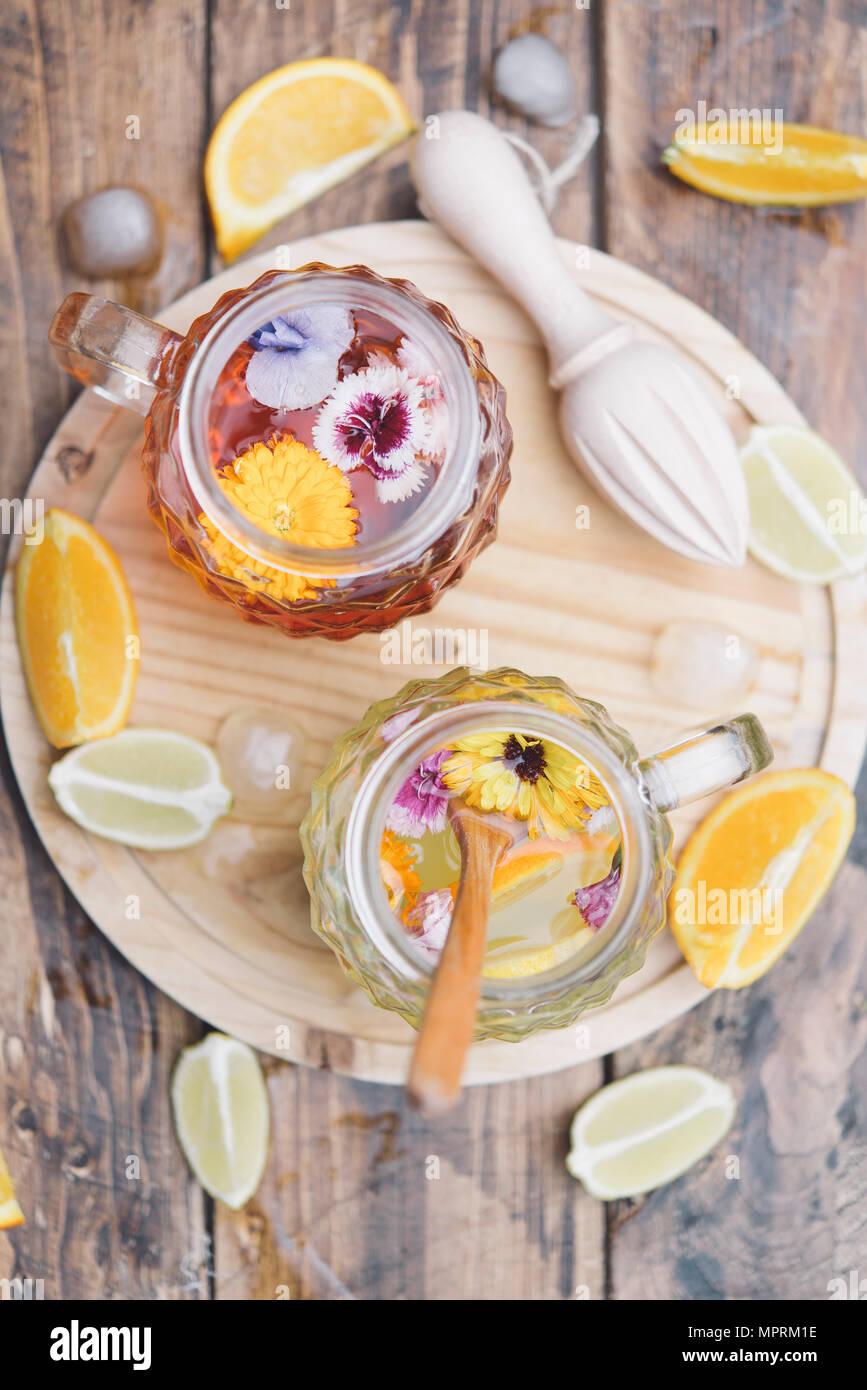 Refreshing mineral water with edible flowers, Viola wittrockiana, Dianthus caryophyllus, Calendula officinalis, lemon and orange - Stock Image