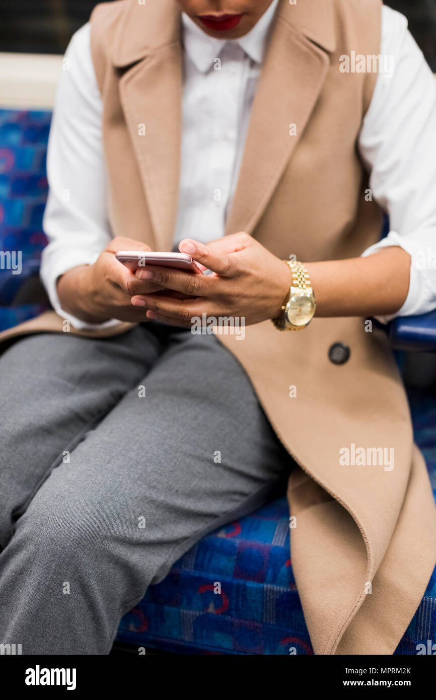 Hand of businesswoman holding cell phone in underground train - Stock Image