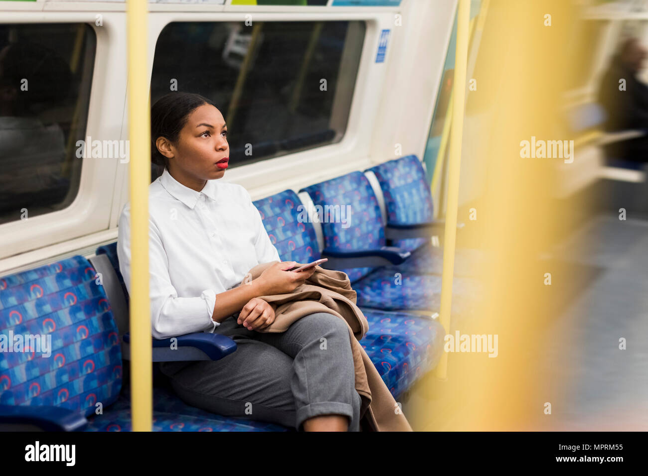 UK, London, businesswoman with cell phone sitting in underground train - Stock Image