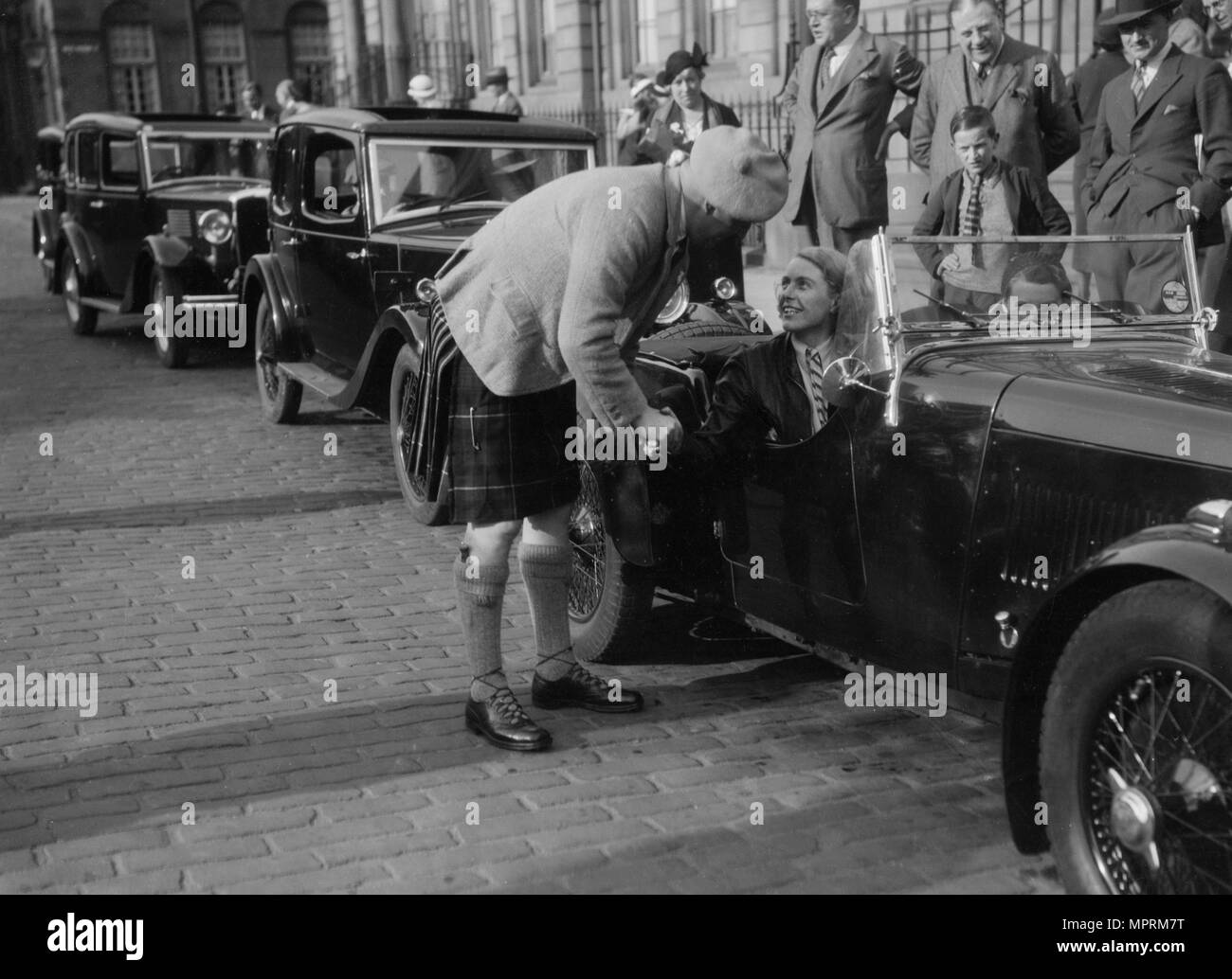Kitty Brunell in her Aston Martin, chatting to a man in Highland dress, RSAC Scottish Rally, 1933. Artist: Bill Brunell. - Stock Image