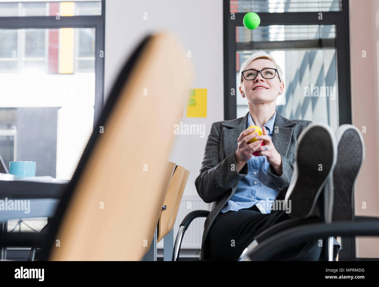 Smiling businesswoman juggling with balls in office - Stock Image