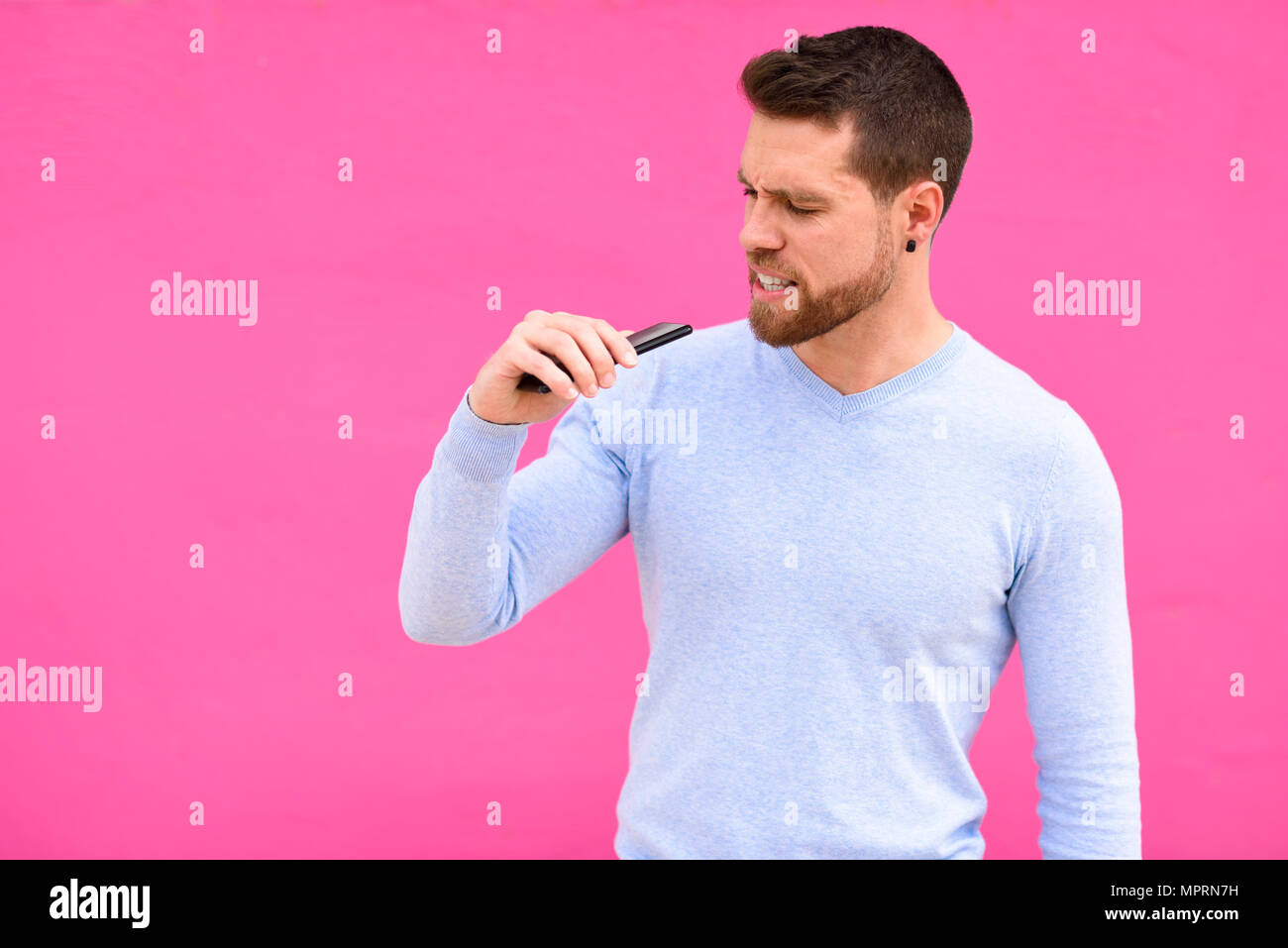 Young man recording a voice note with a smartphone, pink background - Stock Image