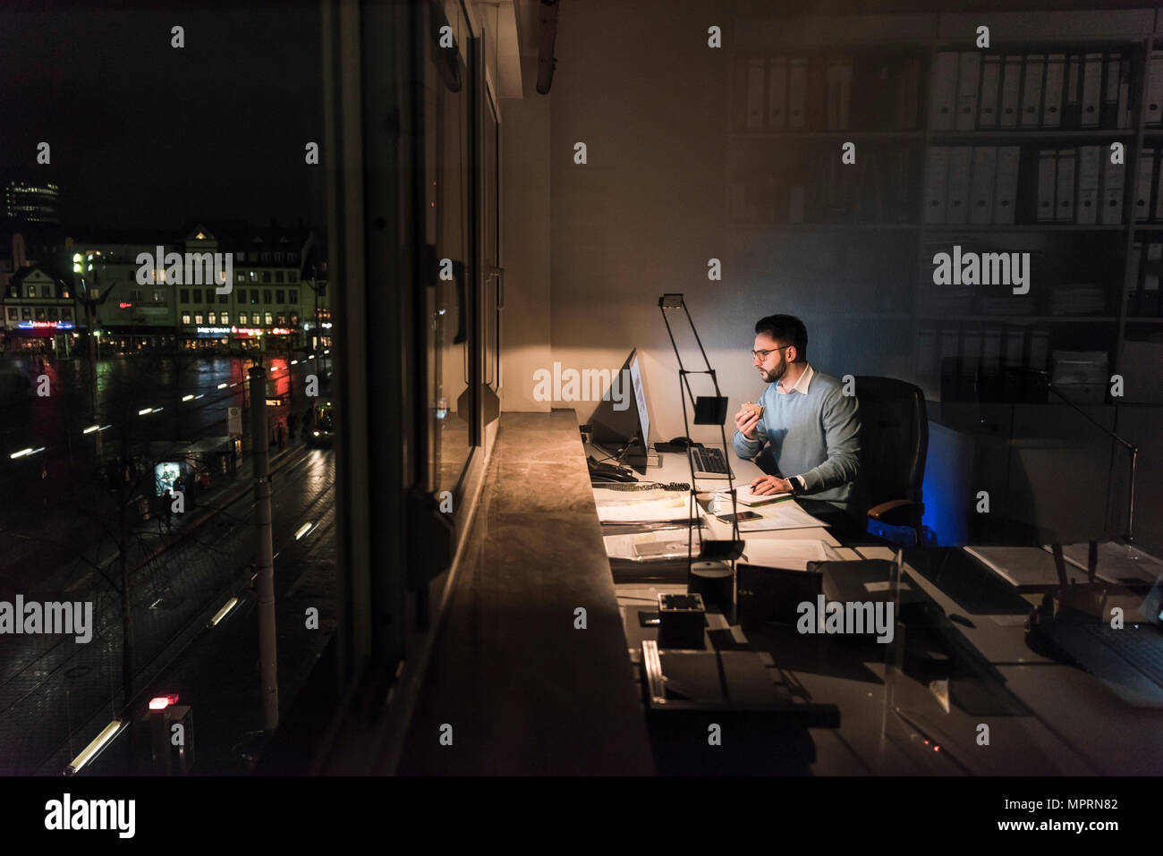 Businessman working on computer in office at night - Stock Image
