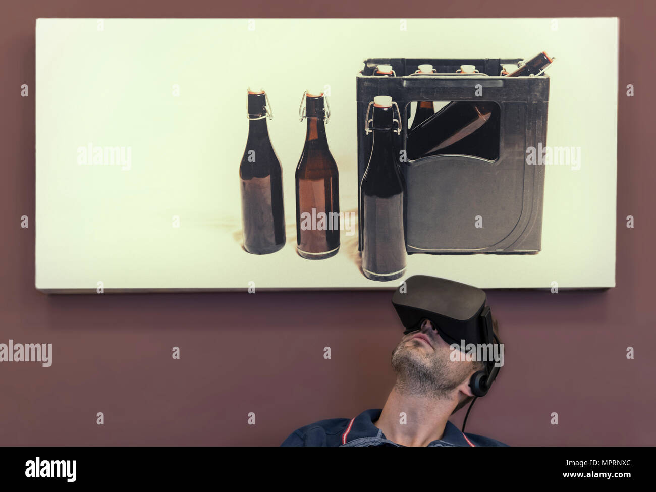 Man wearing VR glasses under photography of beer crate - Stock Image