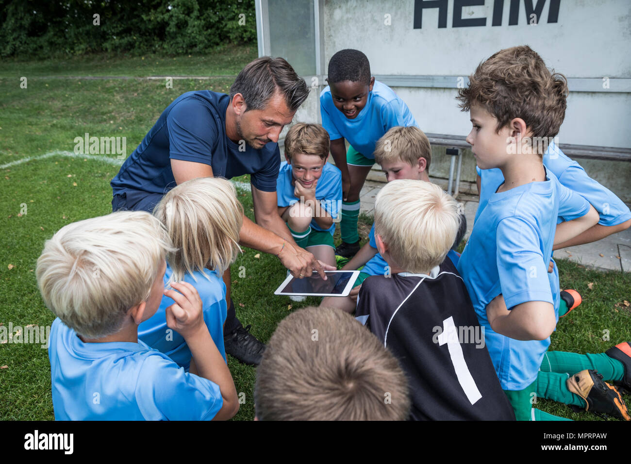 Coach with tablet and young football players on football ground - Stock Image