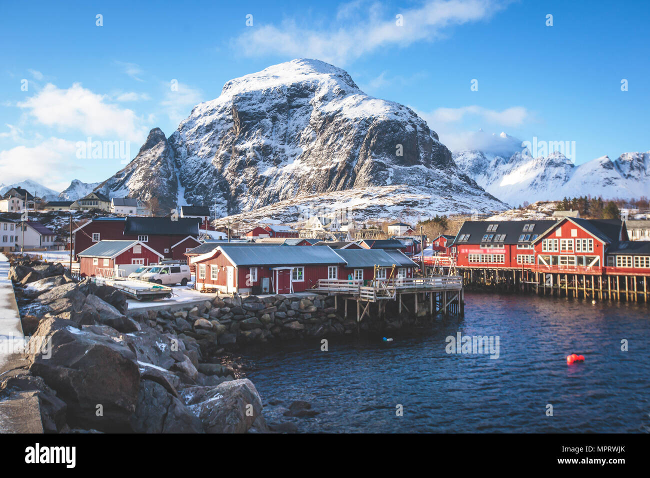 Beautiful super wide-angle winter snowy view of fishing village A, Norway, Lofoten Islands, with skyline, mountains, famous fishing village with red f - Stock Image